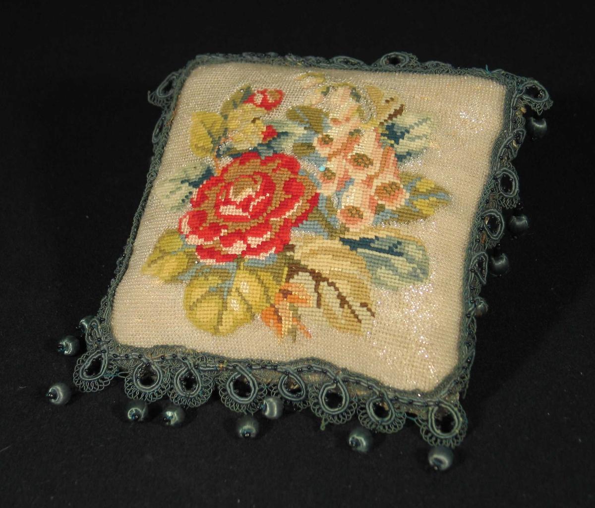Firkantet brodert nålpute; ytterst blanke perler, innerst diamantsydde roser i rødt, blått og grønn-nyanser. Puten er kantet med possementsbord med fritthengende dobber i grønt med svarte perler. Slitt mønstret silkefor på baksiden.