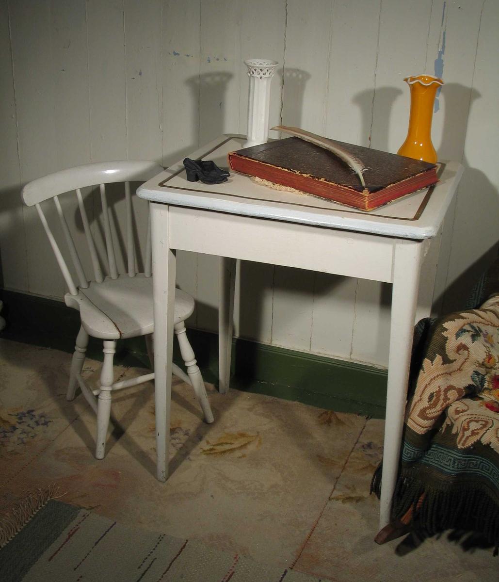 Hvitmalt bord i tre med en centimeter bred gullstriper langs bordkanten.
