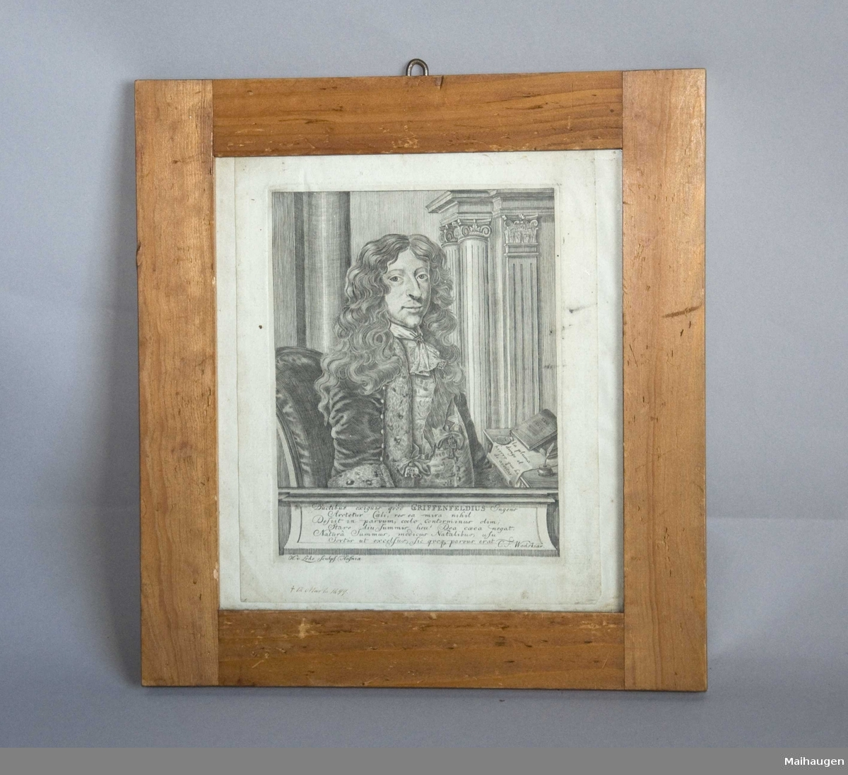 Innrammet kobberstikk. Kobberstikket viser en mann, sittende ved et skrivebord med et skap i bakgrunnen. Skapet har søyler med komposittkapiteler og pilastre med korintiske kapiteler. På skrivebordet ligger en bok og et brev. Boken er merket LEX REGIA - Kongeloven, som Griffenfeld utarbeidet i 1665.