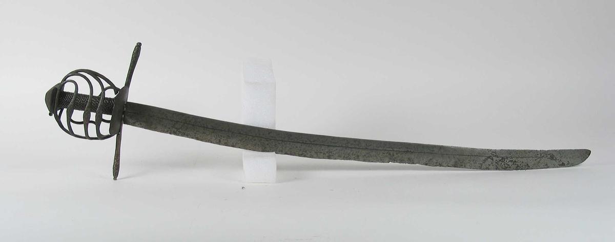 Pyramideformet knapp.  Asymmetrisk kurvfeste med tre sidebøyler som har riflede fortykkelser på midten mellom håndbøylen og kurvens ytterkant. Innsiden har 2 sidebøyler.Tommelbøyle mangler. Kurvens basis er en rektangulær parérplate. Rette parérstenger ( den fremre er nyere og klinket på ) med riflet dekor på endene. Tregrep med jerntrådvikling. Enegget krum klinge med midtstillt smal hulslipning. Rester av smedmerke formet som et øye.