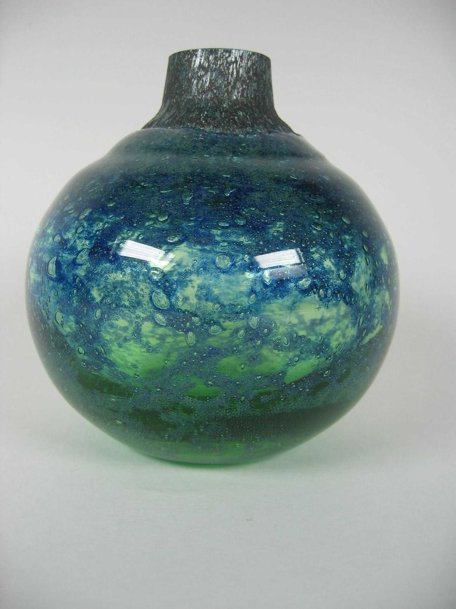 Kulerund vase med lav sylindrisk hals. Vasen er laget ved at et lag grønt glass har fått lagt på et lag blå masse hvorpå det legges et lag klart glass. Det klareglasset dekker ikke halsen og øvre del av vasen.
