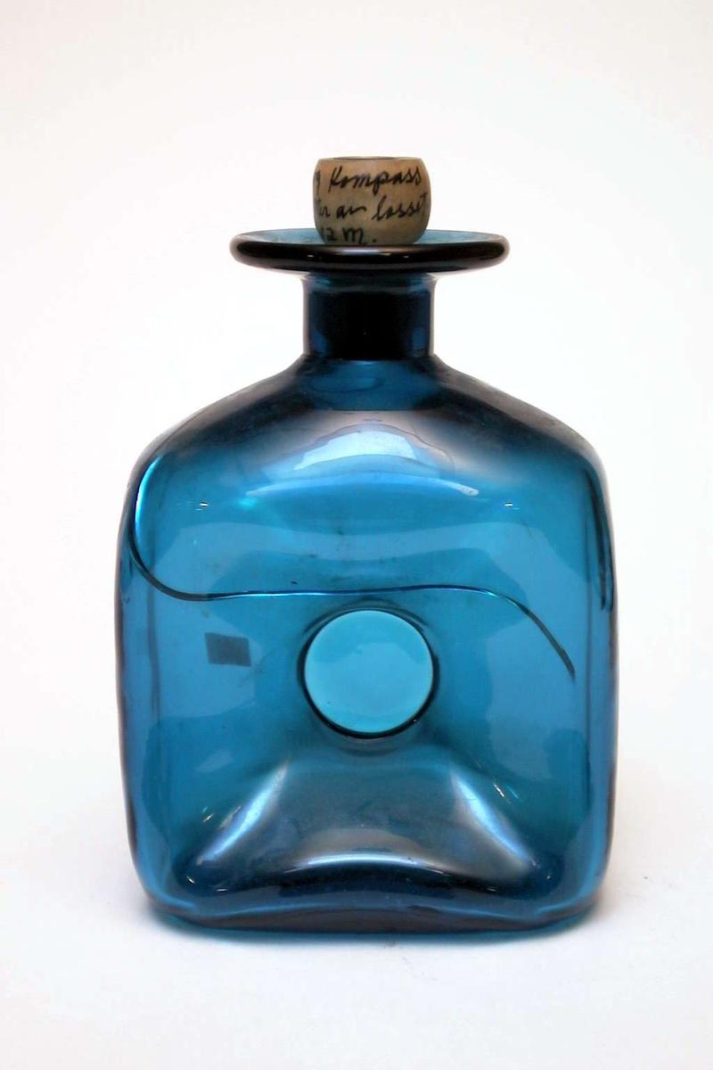 Blå karaffel med kork med kompass på toppen. Glasset er sprukket. Usikkert om korken er original.