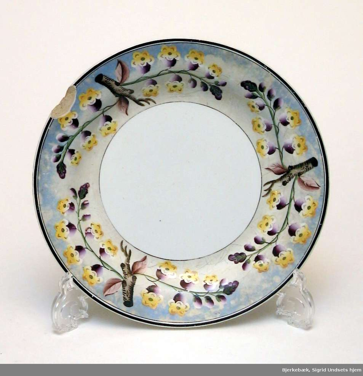 Tallerken i kremfarget keramikk med blomsterdekor i lilla og gult på blå-grå bakgrunn. Det er slått et stort skår av kanten på tallerkenen.