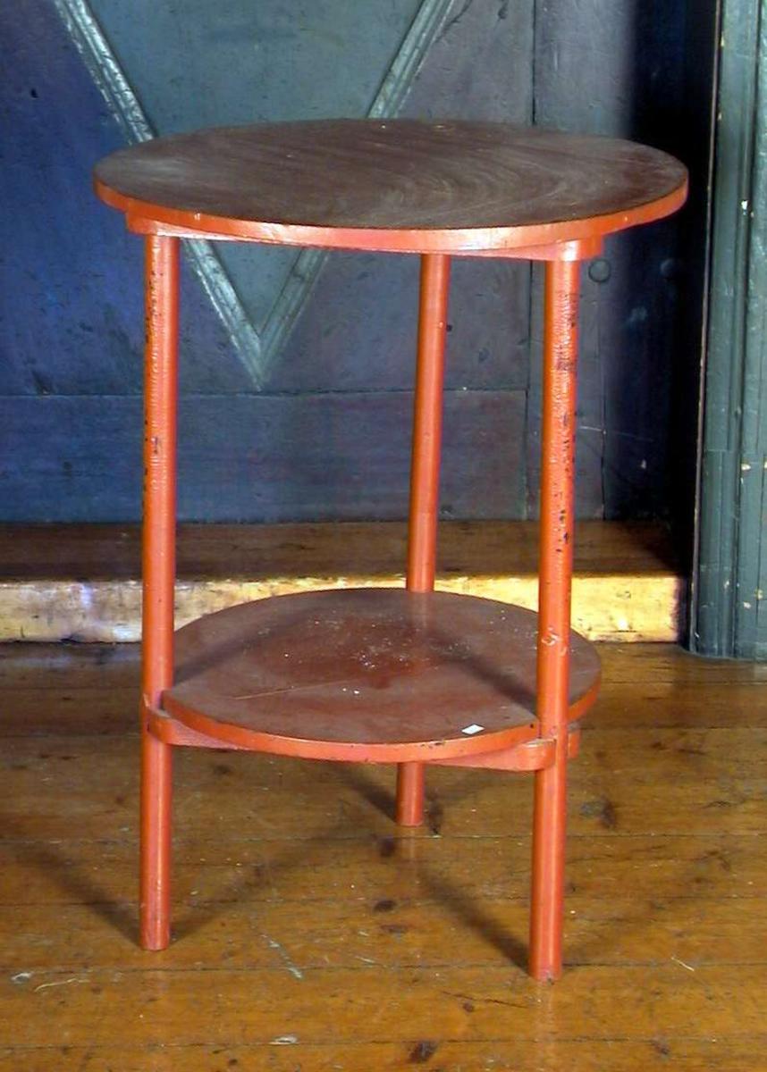 Lite, rundt, rødmalt bord på tre ben. Bordet har plate på benforsterkningene.