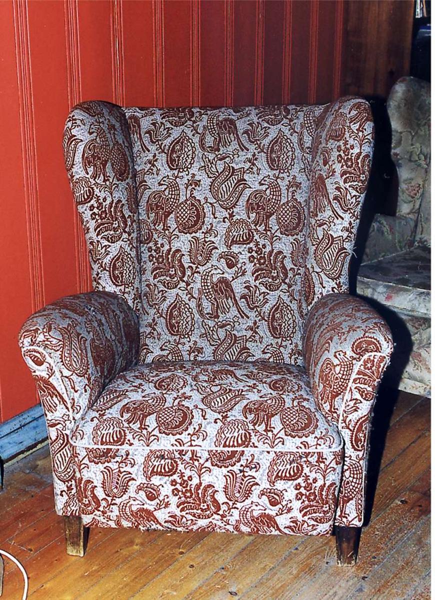 Ørelappstol trukket med mønstret stoff. Stoffet er grått med brunt mønster.