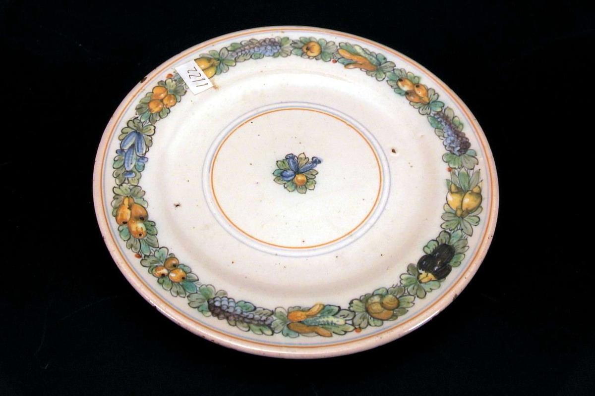 Asjett med håndmalt dekor. Dekorert med frukter, nøtter og rakler i en ring rundt kanten og midt på asjetten. Det er små hakk i glasuren langs kanten av asjetten.