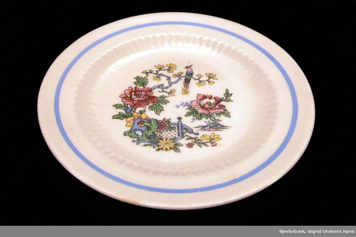 Asjett med hvit glasur og østen-inspirert dekor i blått, rødt, gult, grønt.