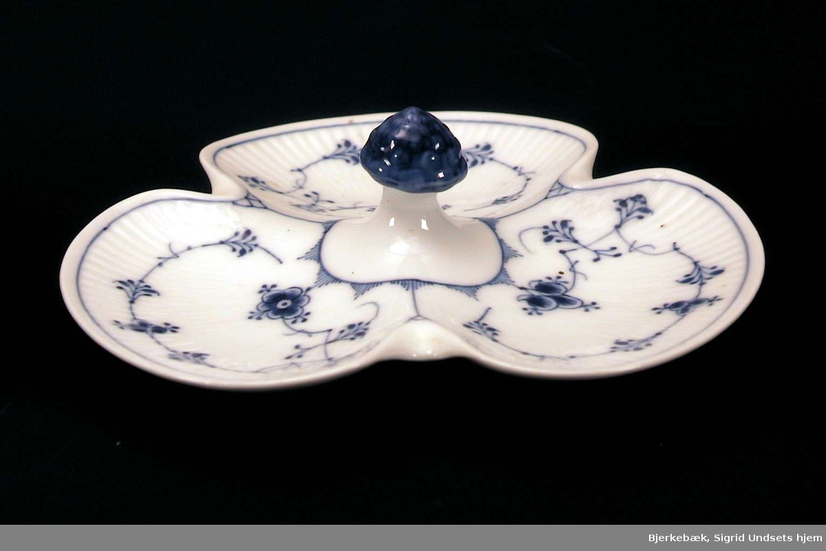 Tredelt skål, riflet, med dekor 'strå' i blått. Midt på skålen et sopplignende grep i blått.