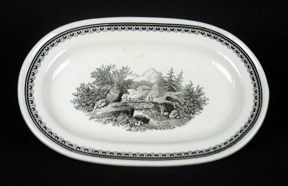 Ovalt fat i benhvit keramikk med sort dekor.