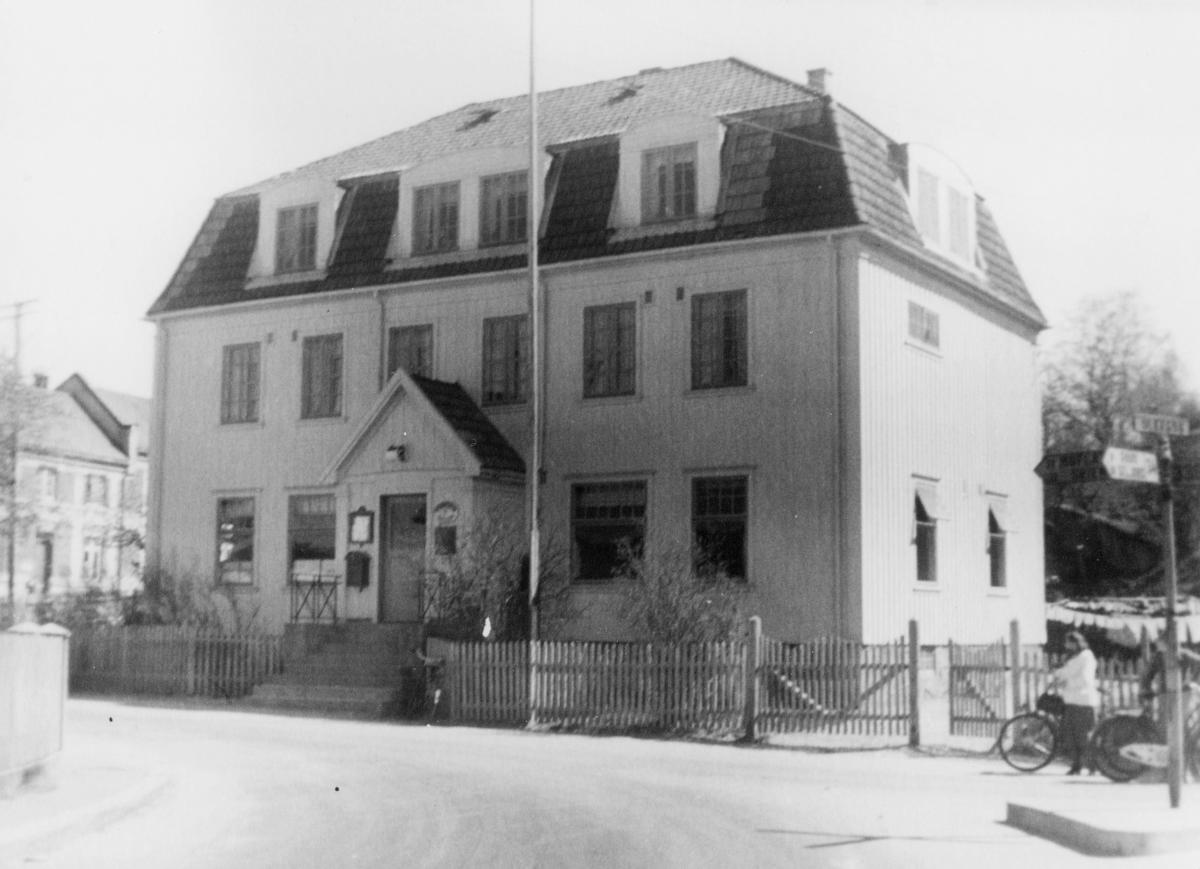 postkontor, eksteriør, Ulefoss, Postverkets gård, postkasse, opplysningsskilt, stakittgjerde, dame med sykkel