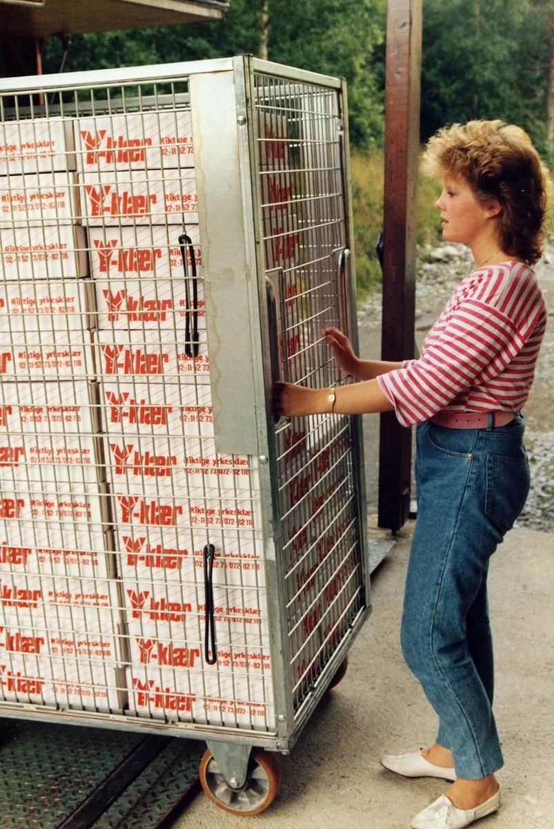 uniform, pakking av Postens profilklær, triller ut en full container, kvinne