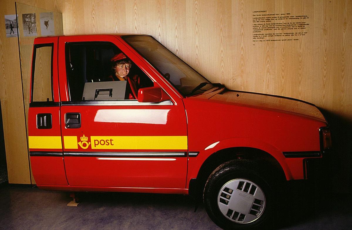 postmuseet, Kirkegata 20, utstilling, landpostbud med rød postuniform i postbil på vei ut med post