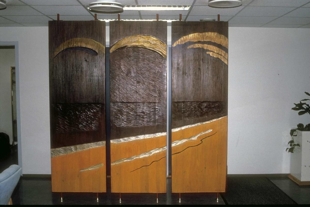 Utsmykkingen består av en skillevegg som består av 3 plater som er festet i gulv og tak.