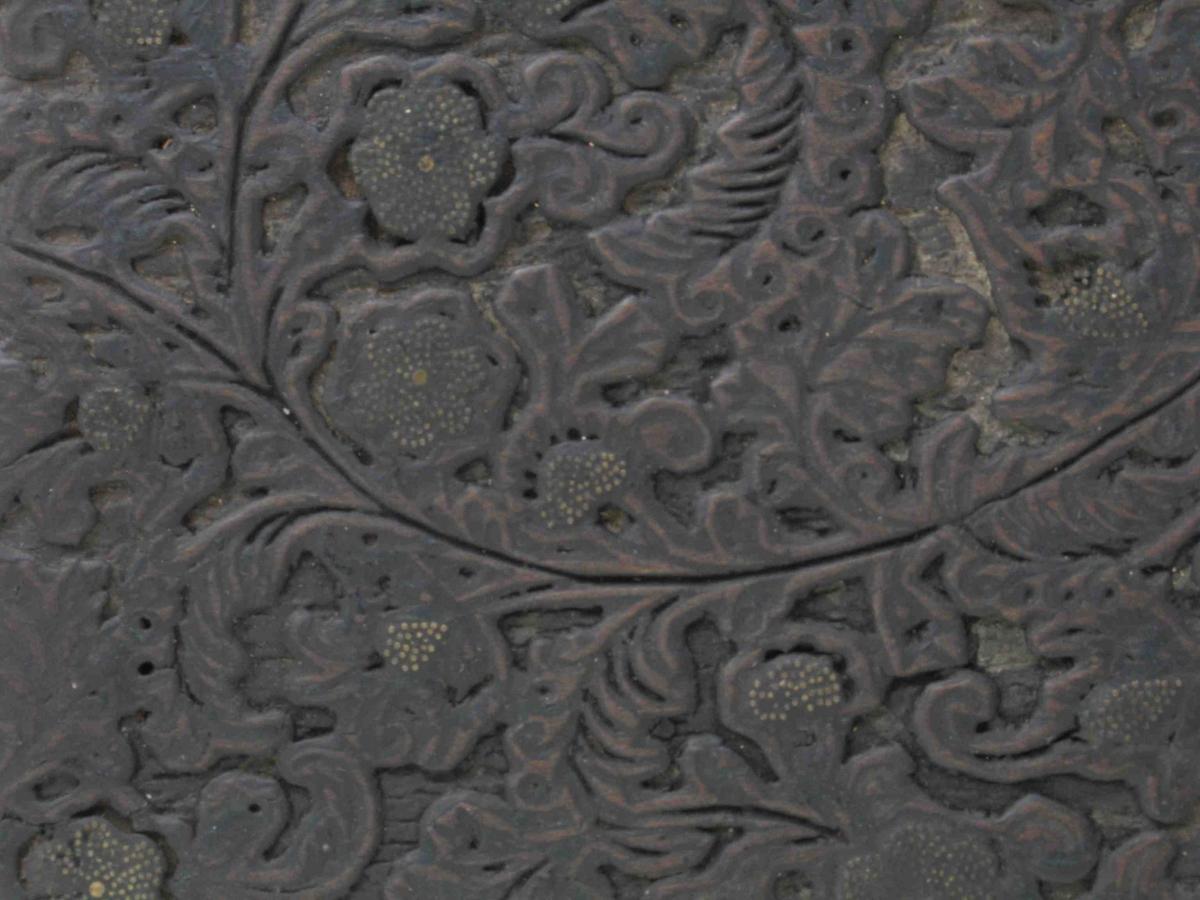 Meget fint skåret tett, tynt   blomstergrenmotiv  som fyller hele platen. Blomster av påstiftede  yr ess spiker som danner frøkurv.