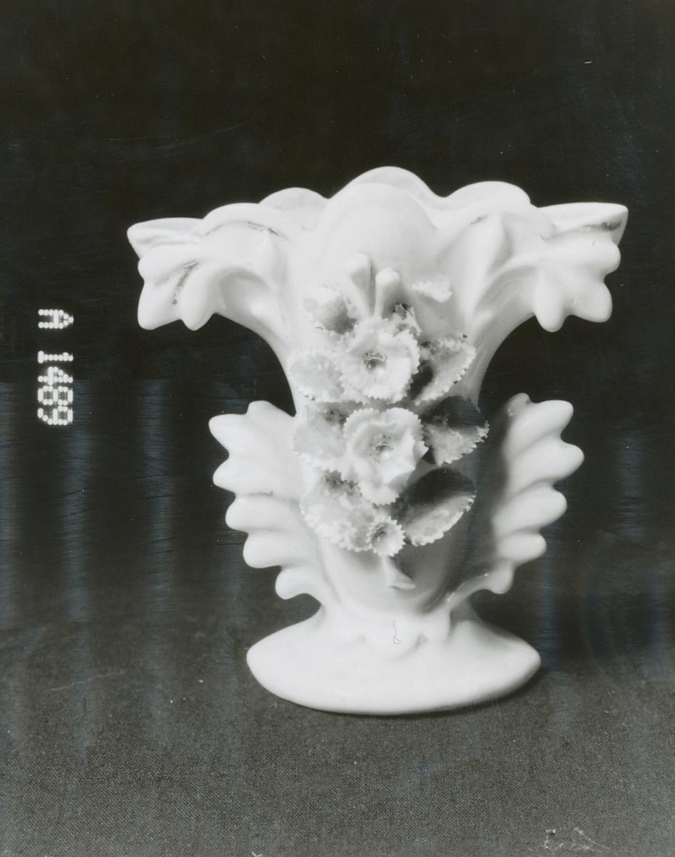 """blomstergren i kraftig relieff på forsiden, """"ører"""" i form av bladløv"""