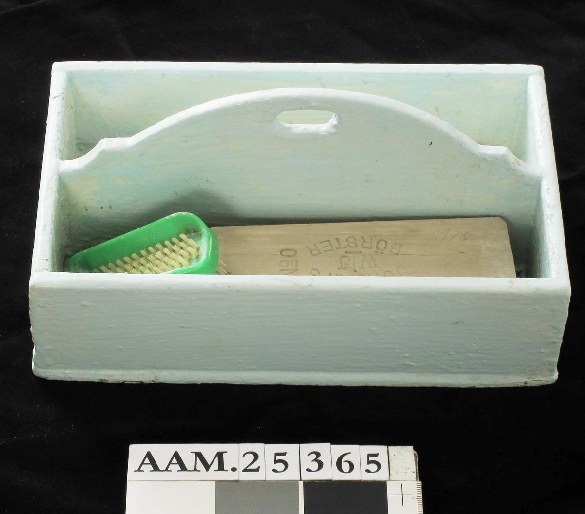 Knivkasse (bestikk kasse),  Opprinnelig lyst ekemalt, nå lyst blåmalt tre.  Rektangulær, lav kasse, delt langsetter i to smale rom ved midtplate med slakt buet overkant hvori liten håndtaksåpning. I hvert rom ligger blå og hvitrutet kjøkkenpapir i bu Knivkasse var vanlig sløydoppgave for gutter i folkeskolen. Kassen bruktes til oppbevaring av stålbestikk m. sort skaft