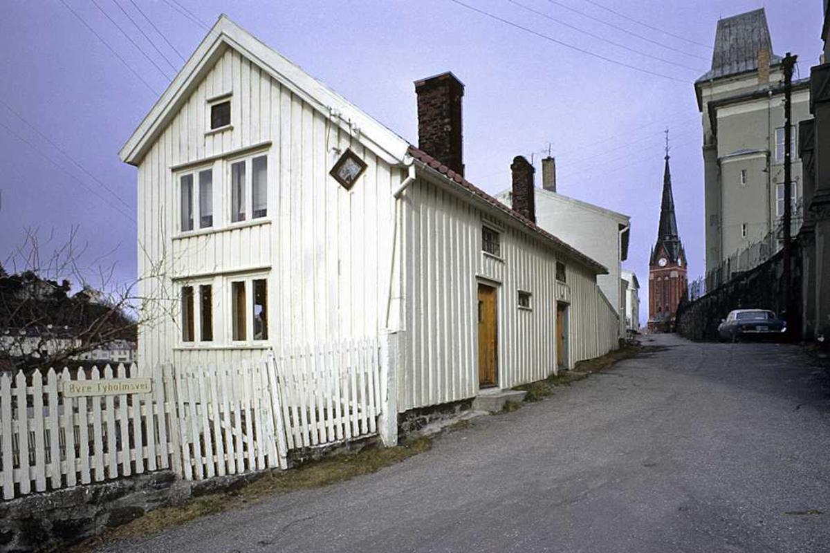 Øvre Tyholmsvei mars 74 . Gateparti, gavl og langside av bolighus, kirketårn, skolebygning