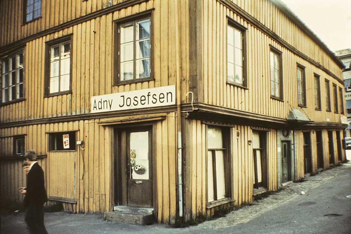 Tyholmen. Det gamle politikammer. Eksteriør hjørnet mot Pollen. Inngang til dagligvarebutikk, med nedrullede gardiner. Skilt Adny Josefsen.