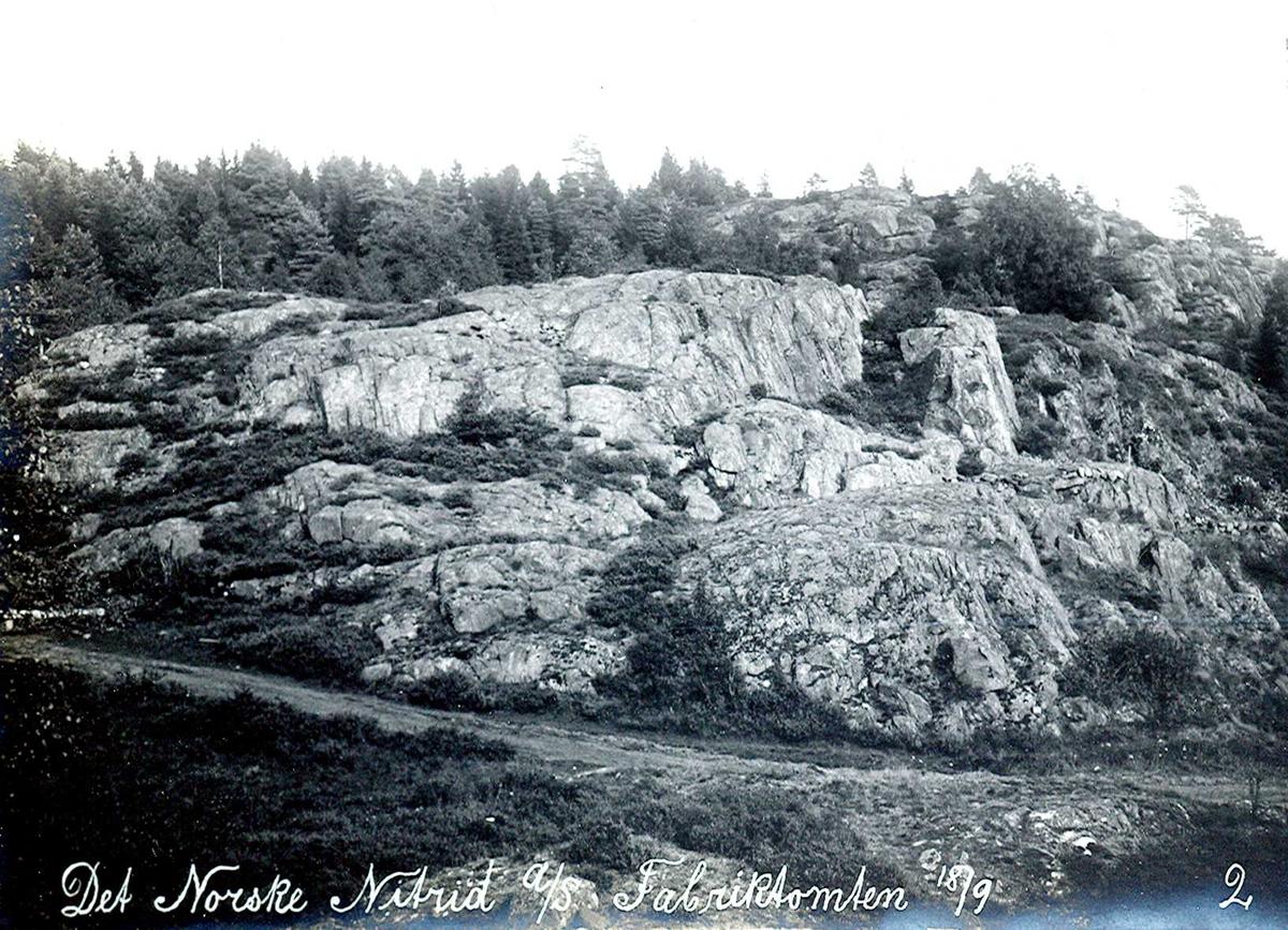 """""""18/09-1912"""" Nitriden. Fabrikktomten. Veien, senere trasé for skinnegang til elektrodefabrikken. I fjellet til høyre ble under krigen 1940-1045 skutt ut tilfluktsrom. På høyden til høyre ligger høydebassenget for trykkvann til bedriftene."""