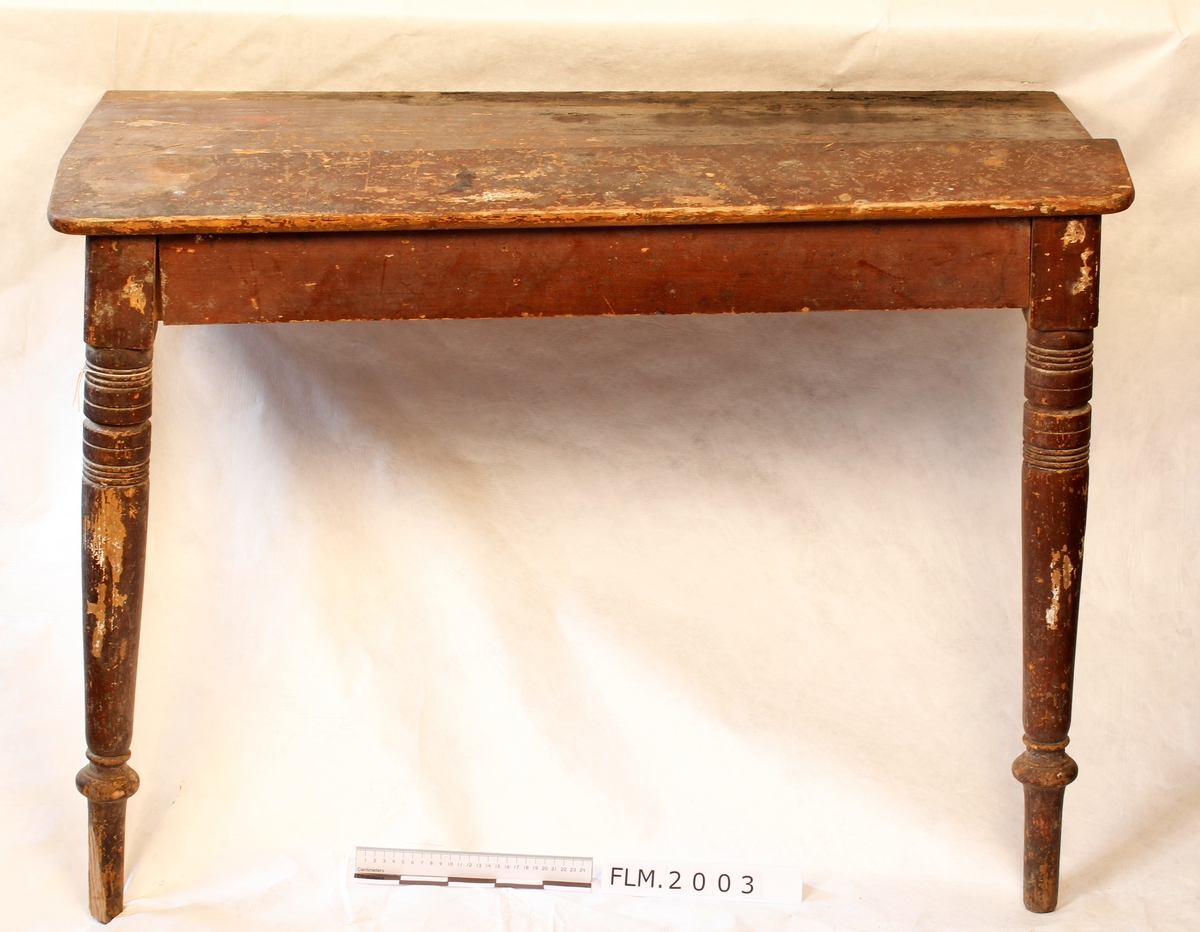 Arbeidsbord som tidligere stått på utstilling i Trådbua.  Har troligen vært brukt på Fetsund Lenser. Bordet er laget slikt at det kan demonteres.   Mangler to bein og en side.