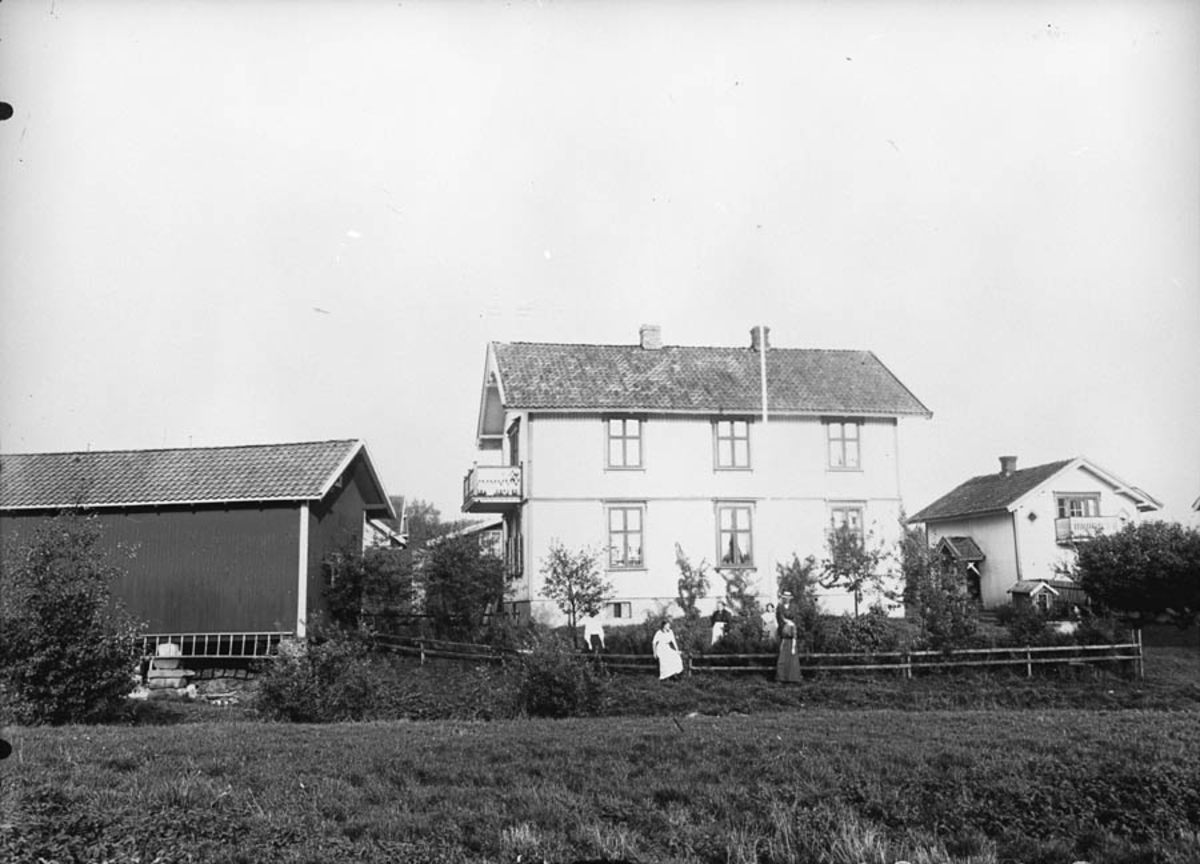 Gammelt hus med 5 kvinner i hagen.