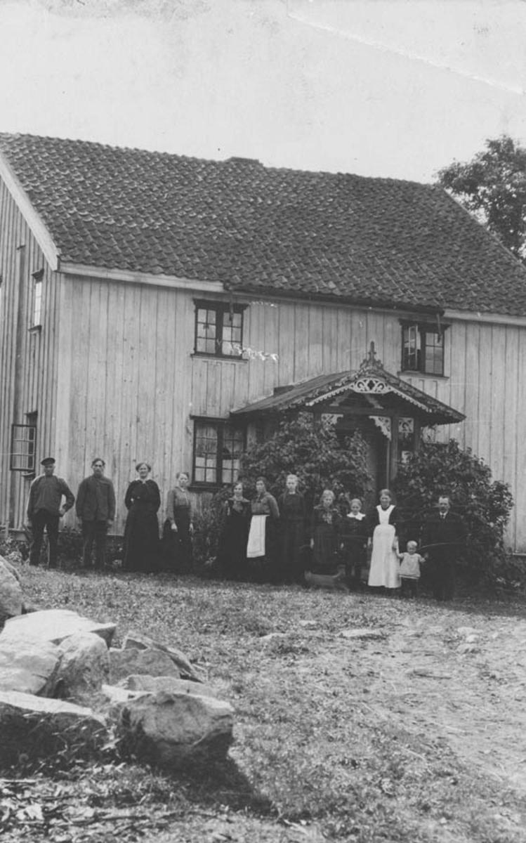 En gruppe mennesker foran våningshuset, Thoug.