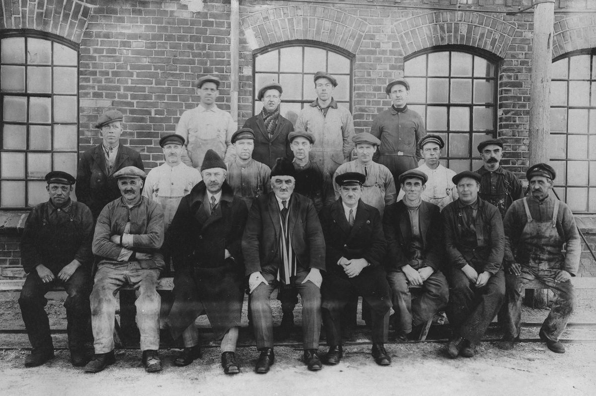 Arbeidsfolk foran teglsteinsbygning