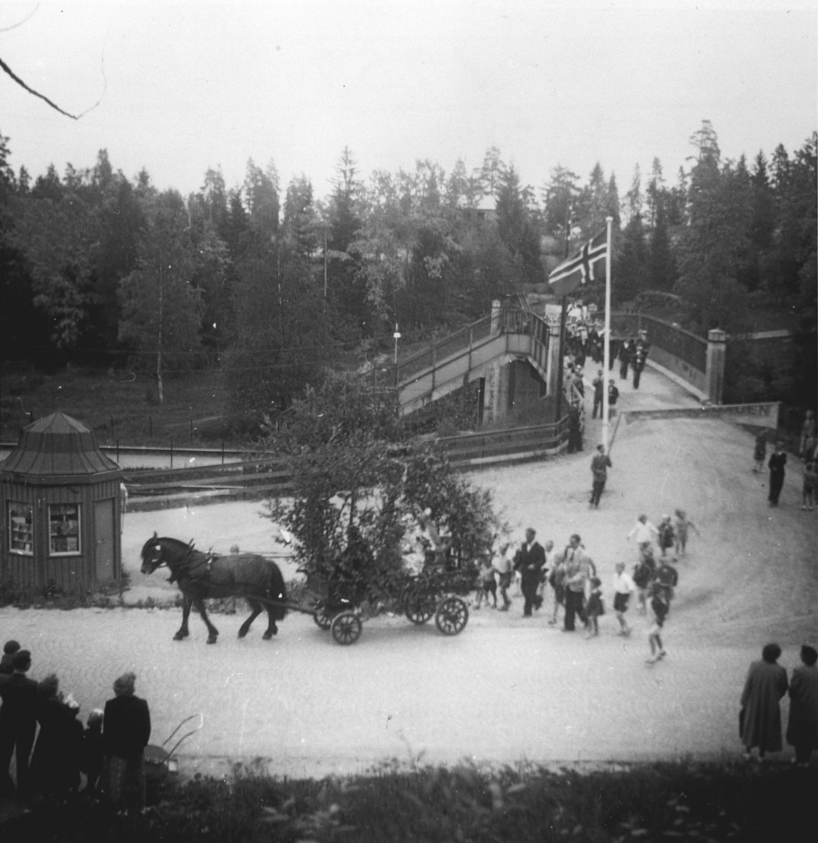 Musikkorps passerer over Myrvollbrua. Hest med løvpyntet kjerre passerer flaggstanga og kiosken.