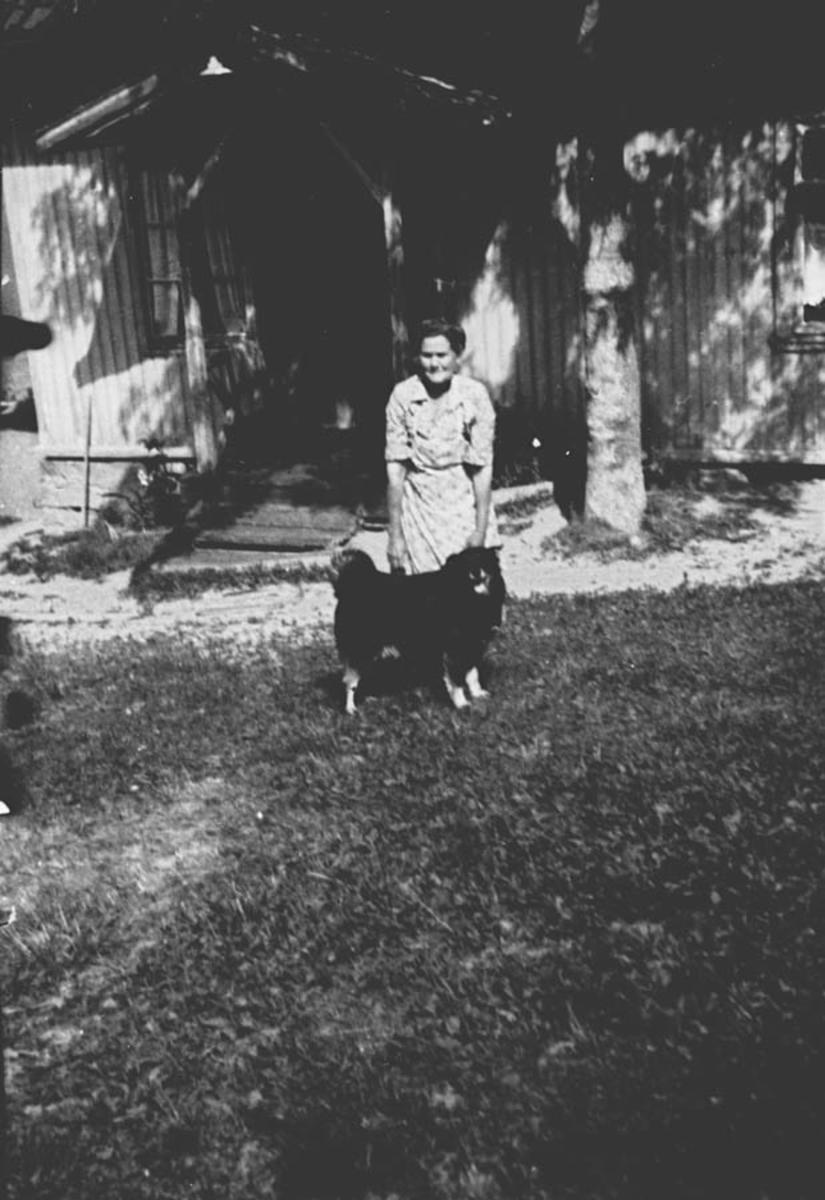 Gard. Kvinne med hund foran hus.