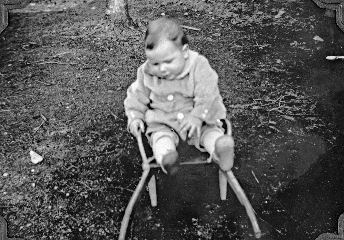 Lars Johan Gjørvad f. 6/8 1934 sitter i si leke-trillebår.