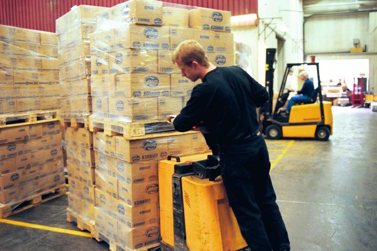 Lagerarbeid, emballasje, gaffeltruck, truck, sjåfør, fabrikkmiljø, arbeider, arbeidsmiljø. Kartonger på paller flyttes med truck