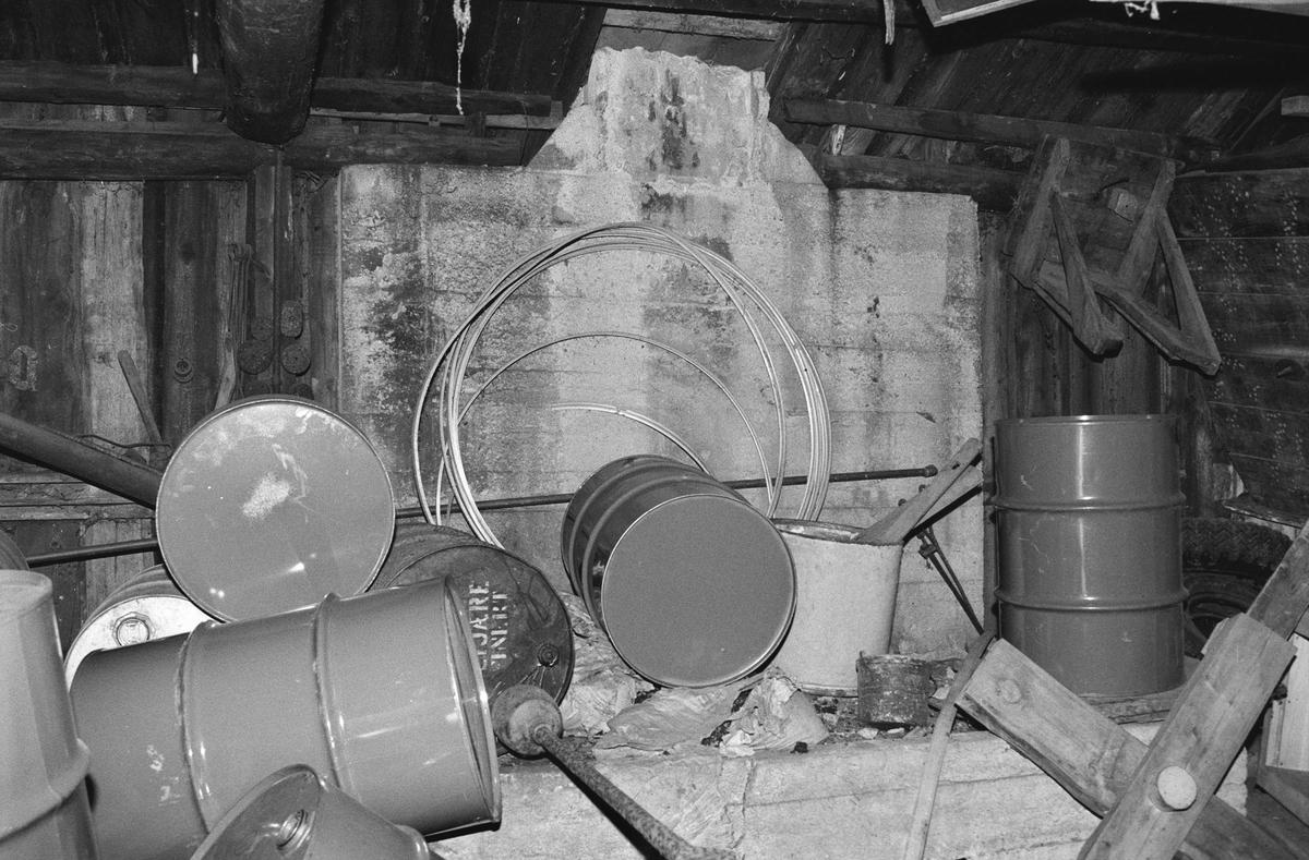 Svartdahl Bruk Interiørbilde fra smia. En samling oljefat, maskindeler og annet skrot