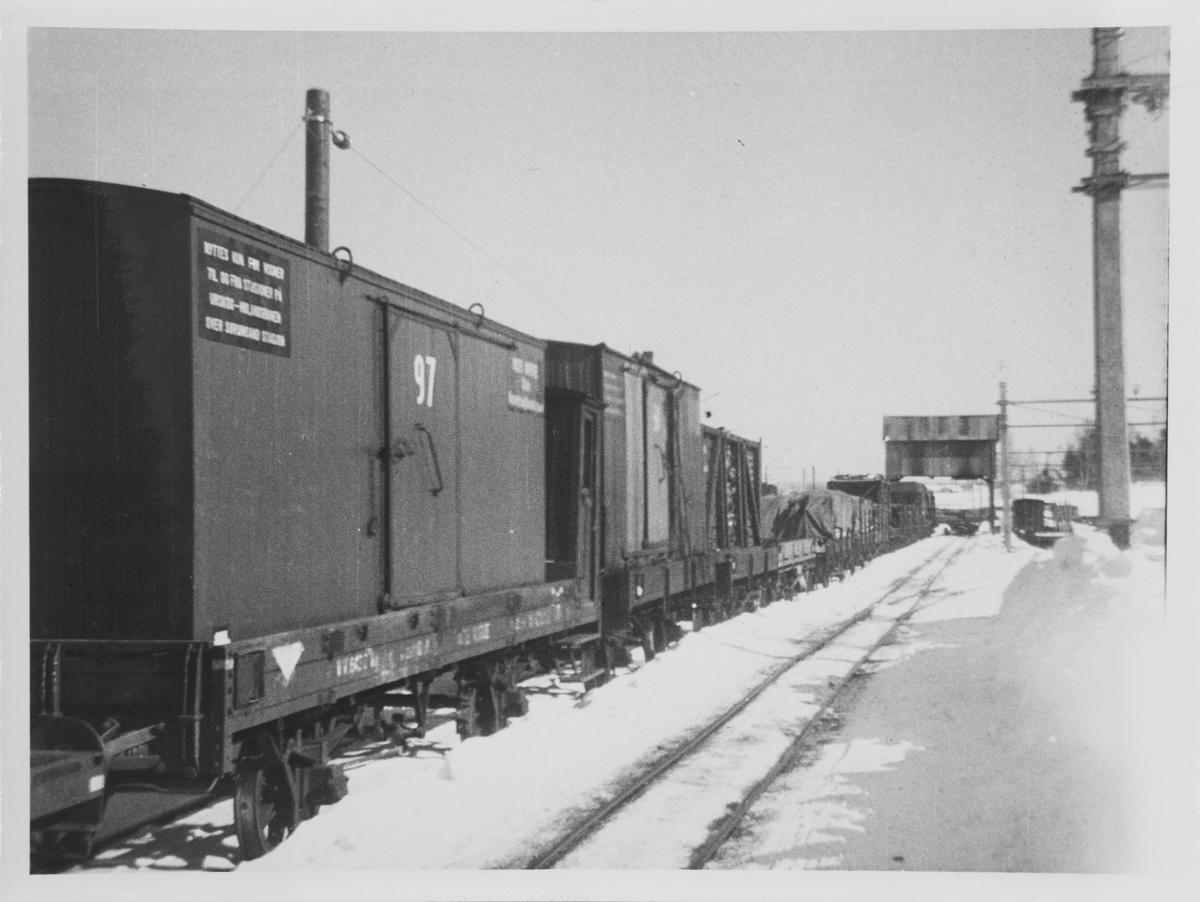 Normalsporede godsvogner med løftekasser og gods som lastes om i portalkranen på Sørumsand.