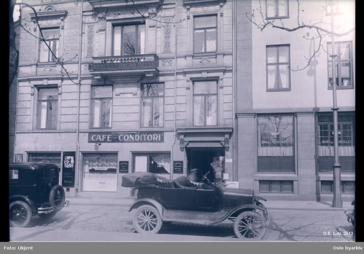 """Fasadebilde tatt fra andre siden av gaten. Biler parkert ved fortauskanten. Butikker - """"Cafe - Conditori"""", """"Tannlege Ragna Brekke"""", """"Bang & Tegner & Co"""""""