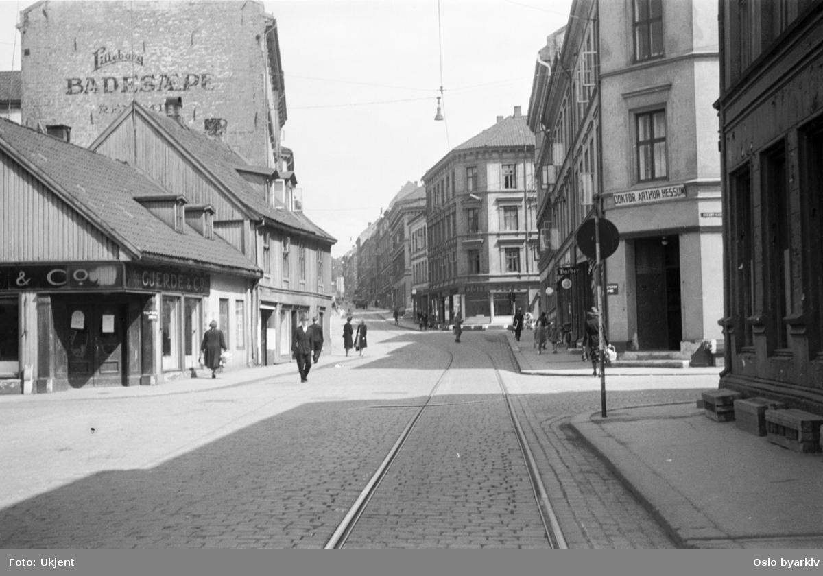 Trikkeskinner, personer. Oppover Tøyengata, i krysset med Nordbygata. Neste kryssende gate er Urtegata.