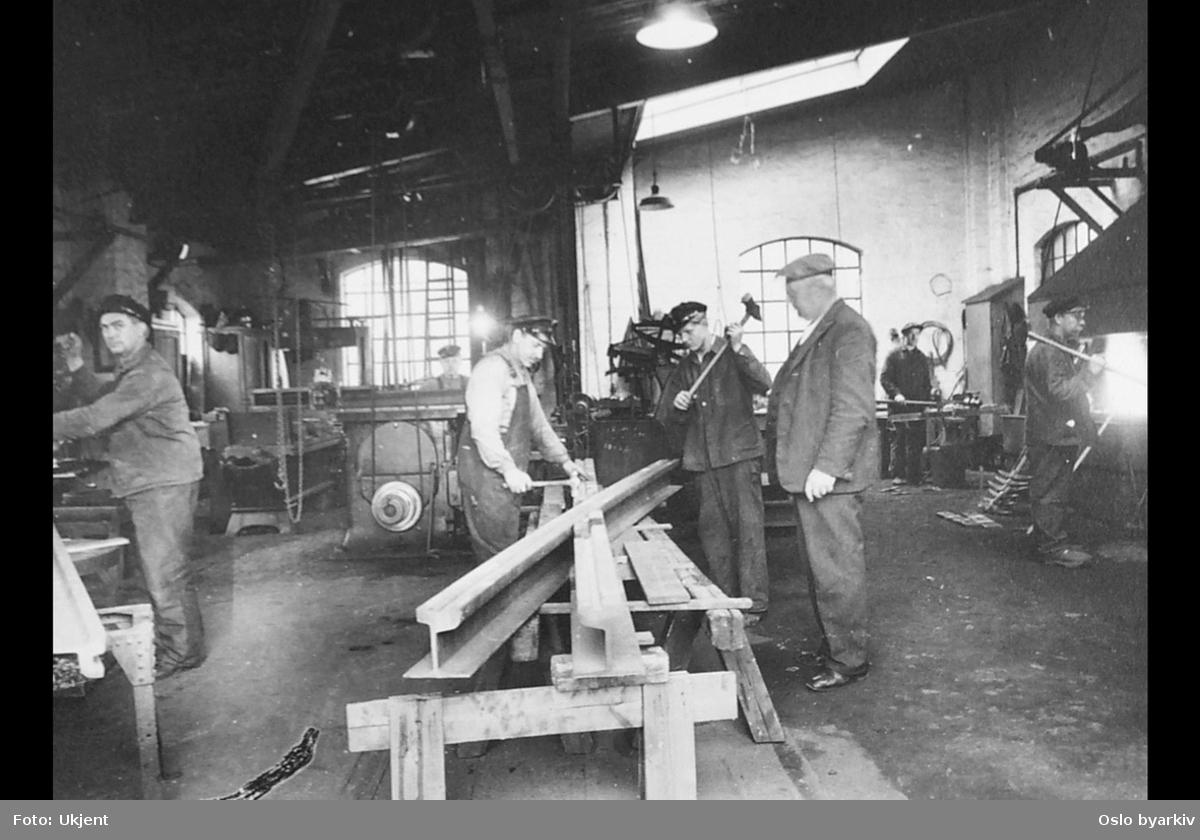Interiør, arbeidere i Sagene vognhall. Aksel Magnus Kjensli ved skinnekrysset i lys skjorte og overall. Mannen til høyre i dress er formannen Røssholt.