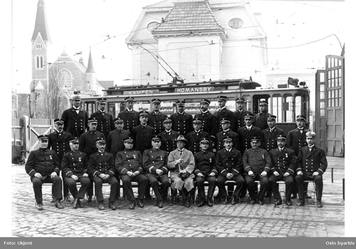 Gruppebilde av overordnede i AS Kristiania Sporveisselskab (Grønntrikken) 25. mai 1923, utenfor vognhallen i Homansbyen. Rett bak sees administrasjonsbygningen. Fagerborg kirke til venstre.