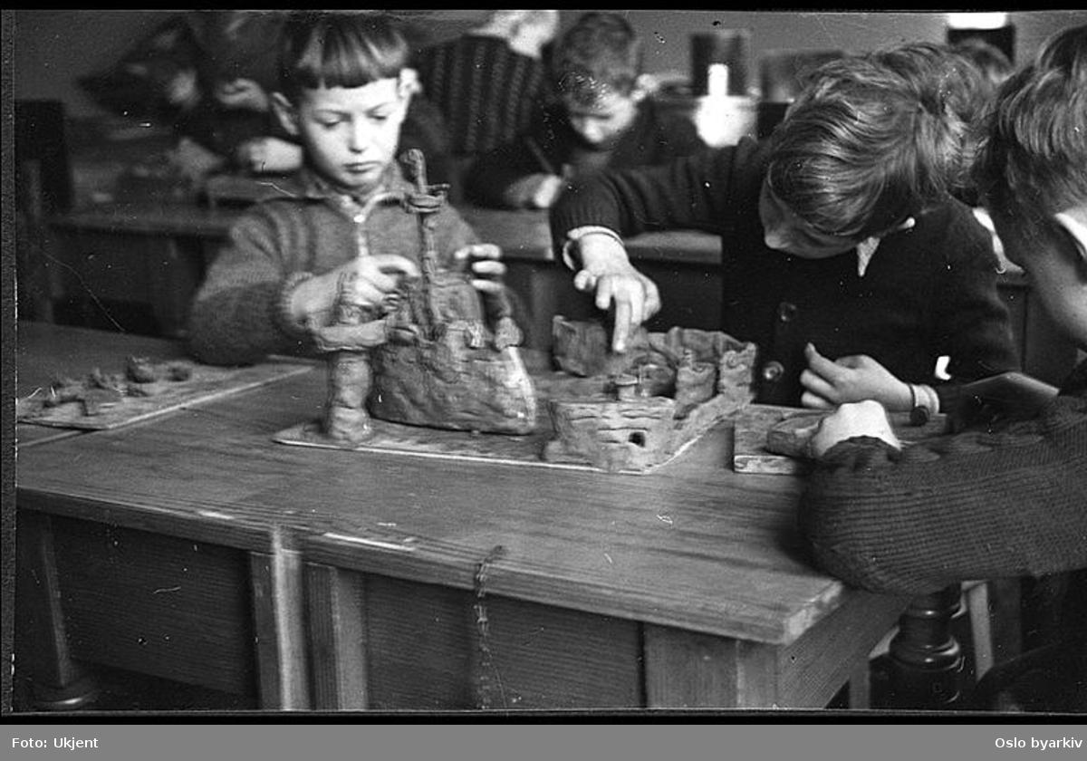 """Gutter modelerer båter (krigsskip) i formingstimen. Albumtittel: """"Sofienberg skole femti år - første september 1933."""""""