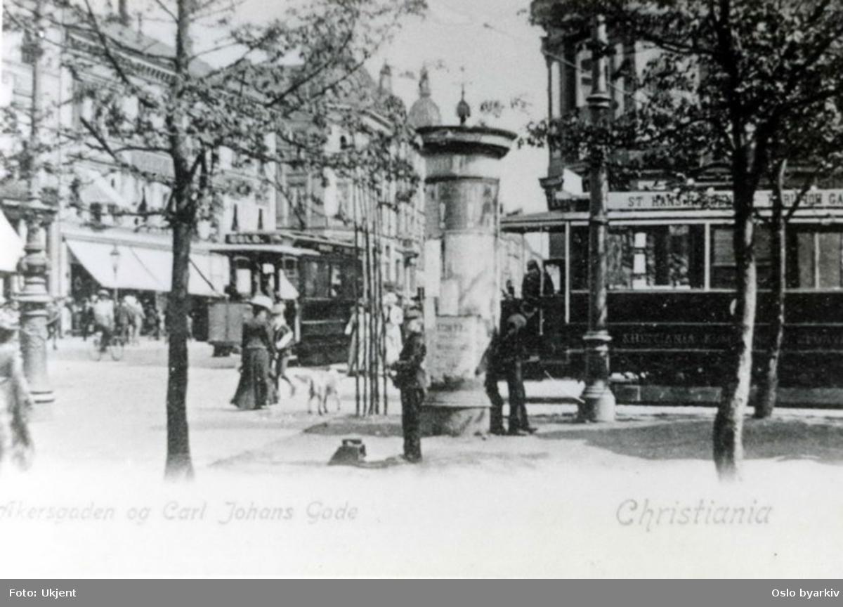 Akersgata krysser Karl Johans gate. Gatemiljø med både hestesporvogn og elektrisk sporvogn. Fra perioden mellom 1894 og 1900. Reklamesøyle.