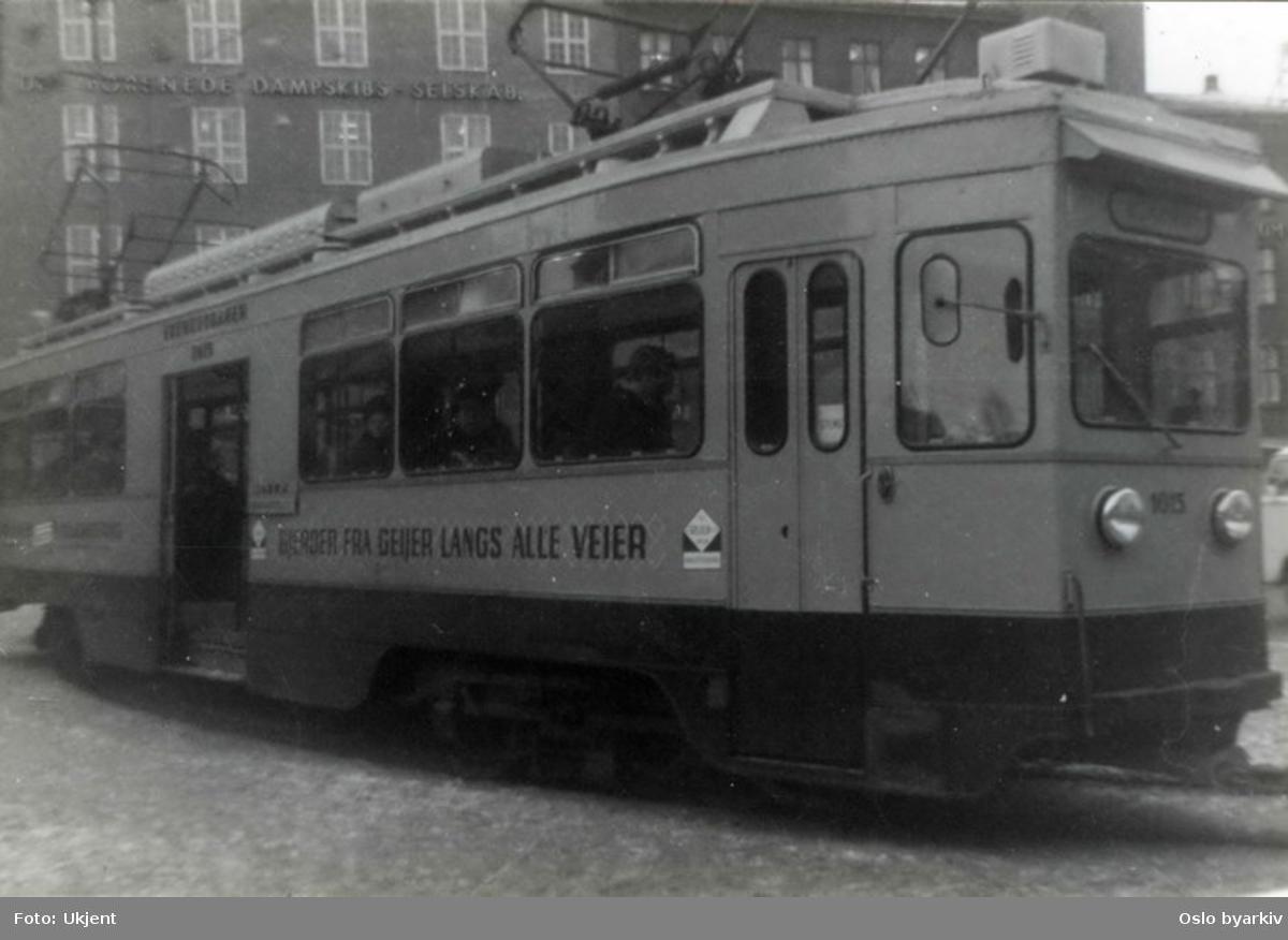 Trikk (motorvogn 1015 fra Skabo, i drift 1933-1974) ved endeholdeplassen på Jernbanetorget på linje 9 fra Ljabru. (Linjen eksisterte mellom 1963 - 1968.) Trikkereklame for gjerdeprodusenten Geijer.
