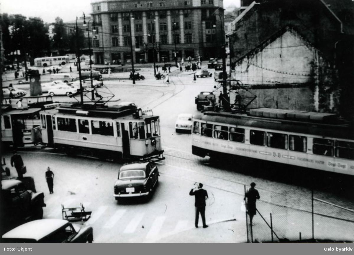 Oslo Sporveier. Trikker (bl.a. Sagenetrikken) passerer ved torget på spor 4 og 5. Trafikkmiljø. Jernbanetorget 2 (Den Norske Amerikalinjes hovedkontor) bakerst. Bildet fra 1960-tallet.