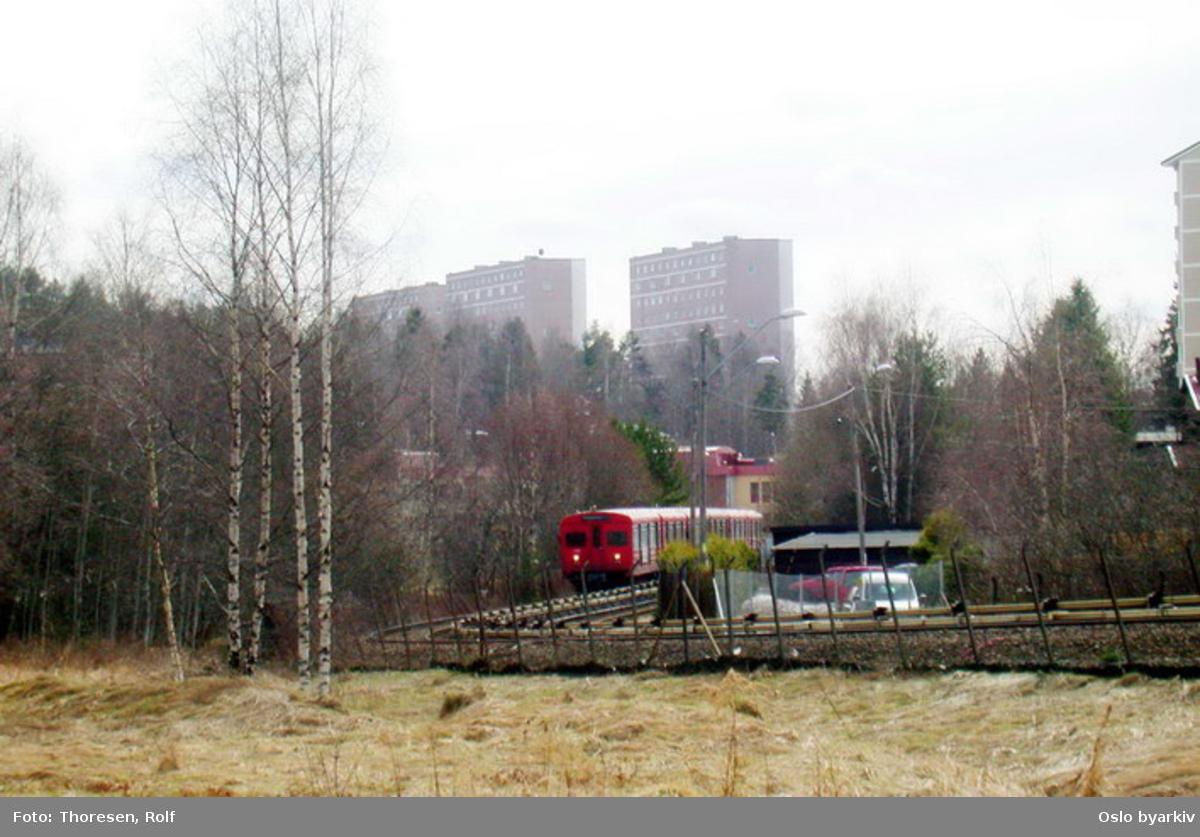 Oslo Sporveier. Østensjøbanen. T-banevogn 1014, serie T1, i tog på linje 3 på inngående, her fra Bøler mot Ulsrud. Høyblokkene på Bøler..