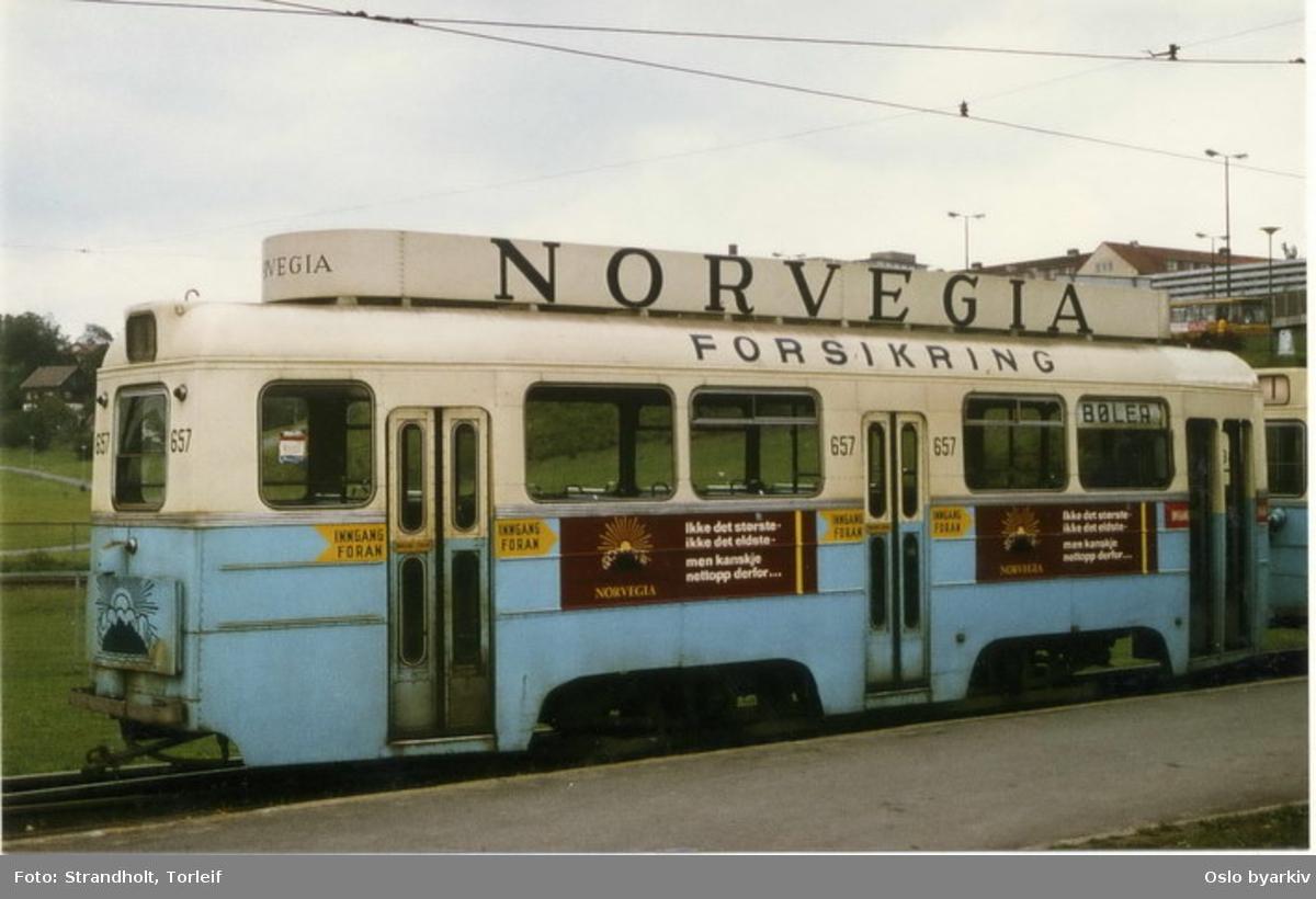 Oslo Sporveier. Trikk Høkatilhenger 657 type TO linje 1, typebilde, fotografen har (feil)skiltet vogna med Bøler, en linje hvortil vogn type TO ikke kunne benyttes. Trikkereklame for Norvegia forsikring. Her ved endeholdeplassen ved Muselunden på Sinsen.