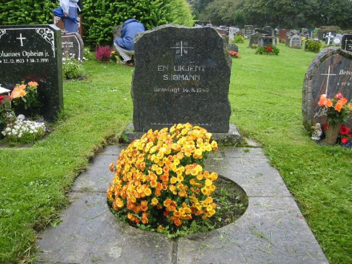 Gravsten H. 0,8 m B 0,7 m D 0,2 m Kors med den evige flamme. Bord i bunn. Hellelagt 2 X 1 m med blomster i midten.
