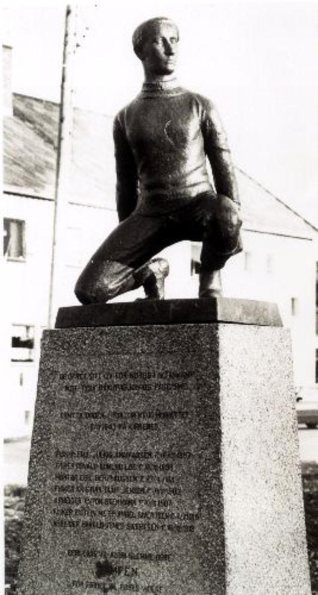 Krigens ofre/Partisanbautaen. Bronseskulptur av mannsperson som står på en steinsokkel