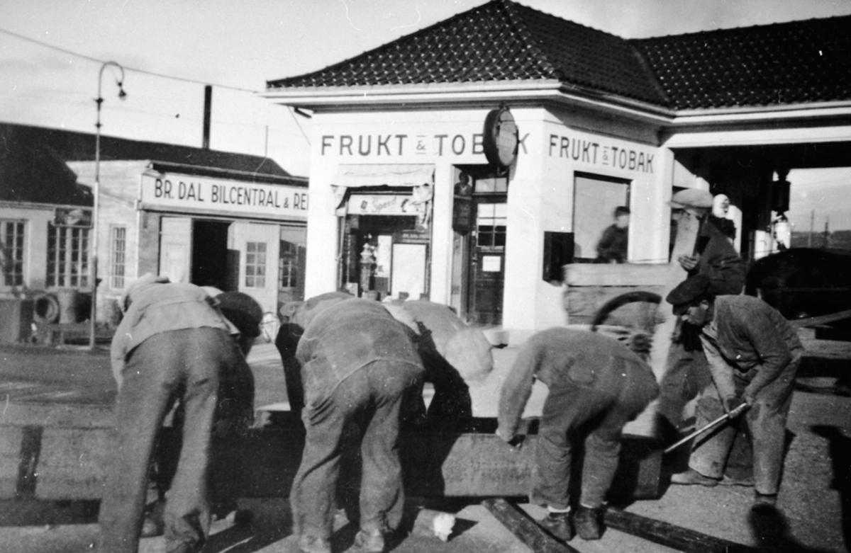 Sandbakkens Frukt & Tobakk, Furnesvegen, Brumunddal Bilcentral, bensinstasjon. Ukjente menn flytter vannledning i tre.