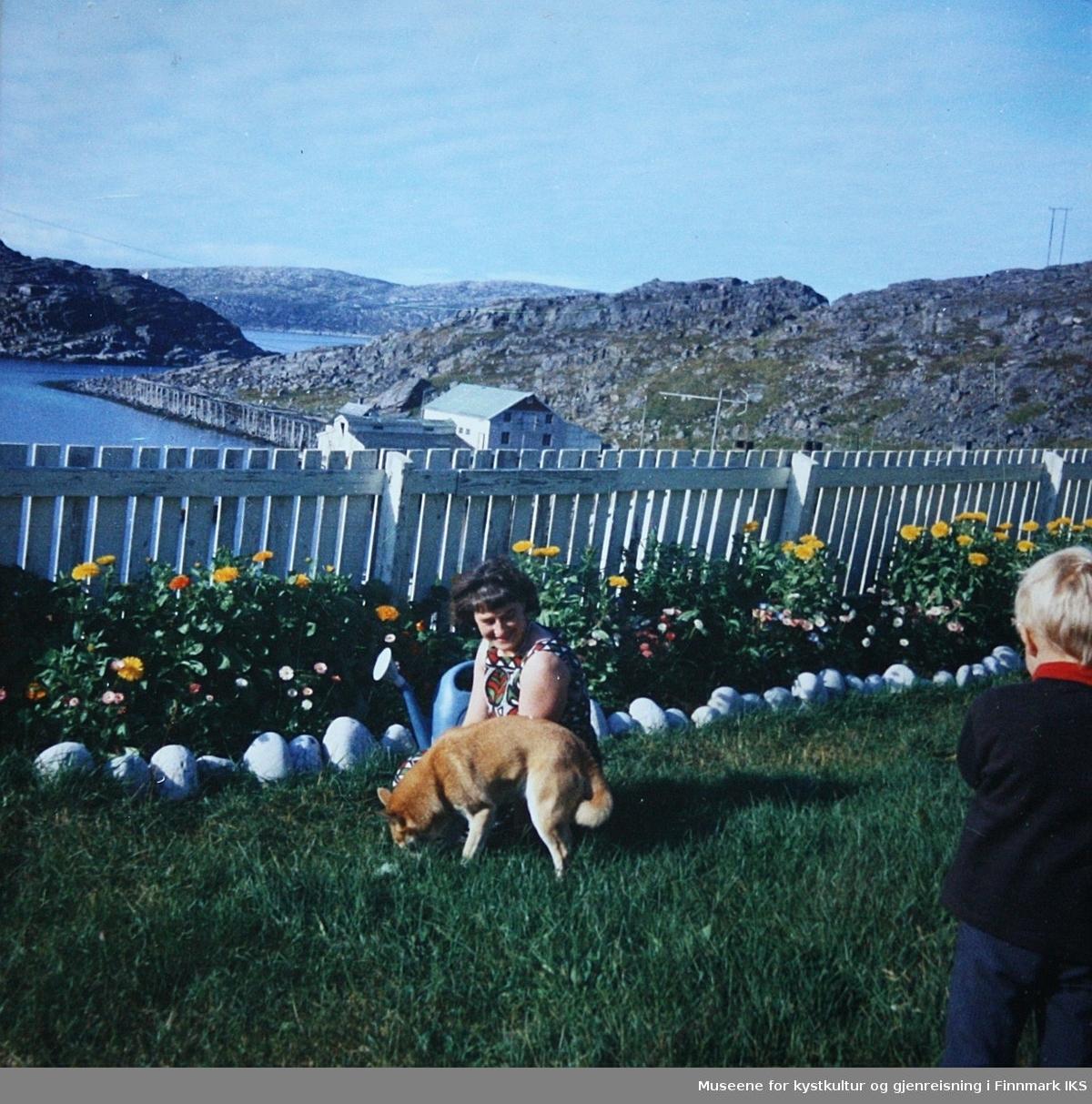 Kvinne, barn og hund  i hagen, Burstad.