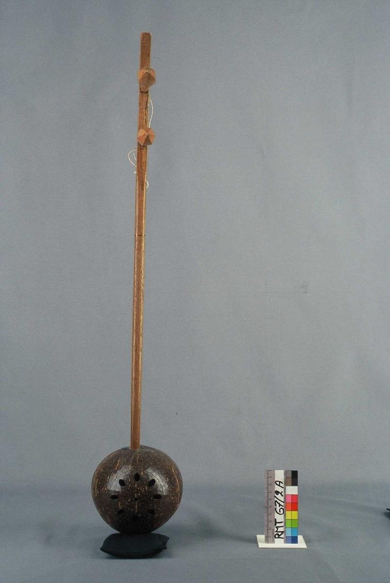 2-strenget. Lakkert korpus, sansynl. kokosnøtt, av nærmest oval form. Lokk av ubehandlet, lyst tre. Bunnen forsynt med ovale lydhull plasert i sirkel. Den avlange, lakkerte trehalsen går tvers gjennom korpus, og ender som kombinert endeknapp og strengefeste. 2 store treskruer, festet undenifra. Et skjell fungerer som stol. Rundt øvre del av halsen og strengene surret en kobbertråd. Buen er stukket inn i mellom strengene og halsen.
