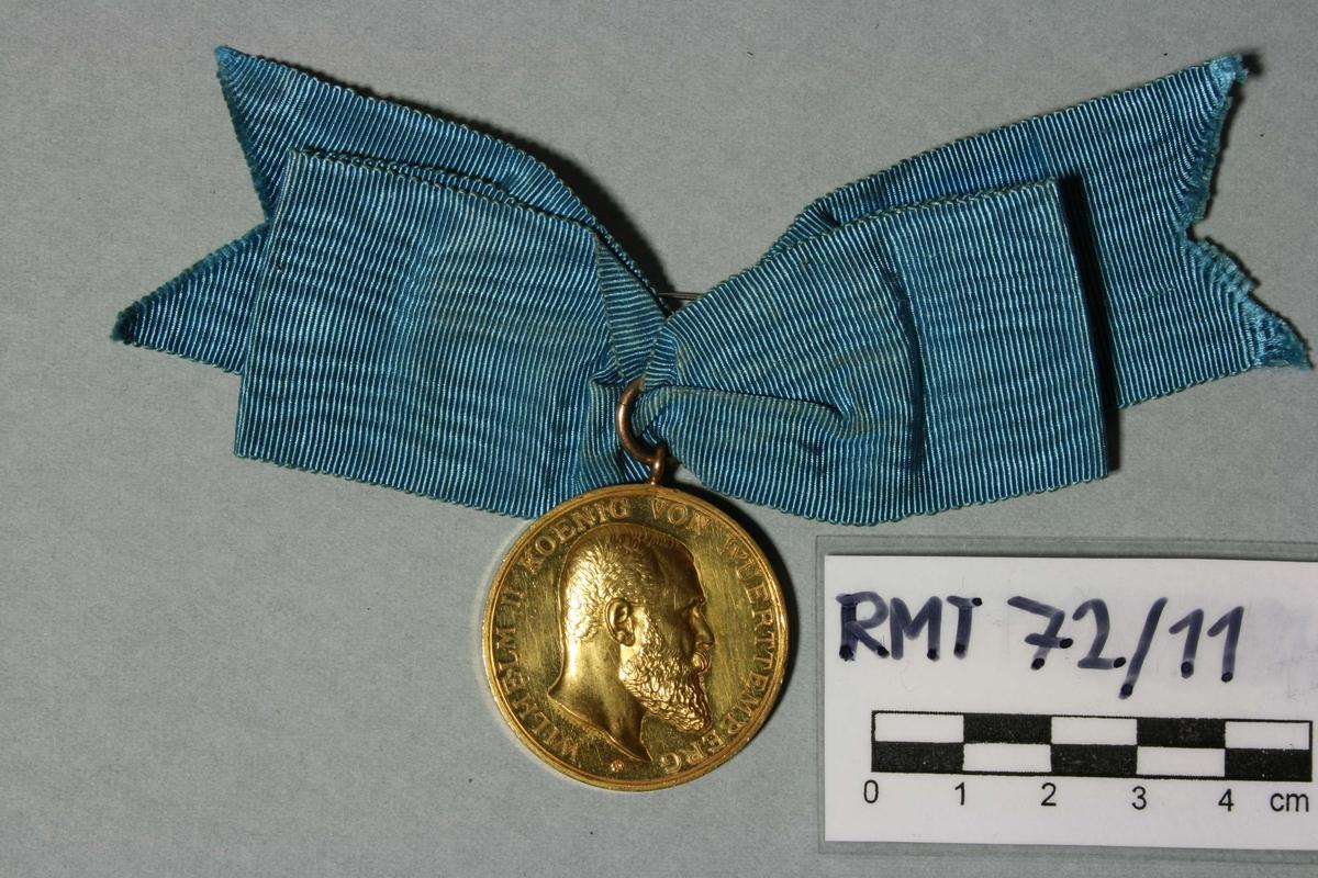 Den württembergske medalje i gull for kunst og videnskap. På den ene siden kongens portretter i profil, haut relief. På den andre siden en gotisk W med krone over. Omgitt av ekeløvkrans. Henger i blå moire-sløyfe.