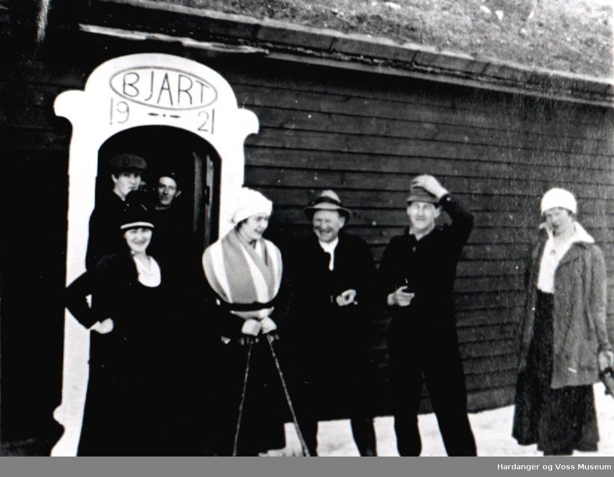 Voss Ungdomslag, skitur, fire menn og tre kvinner ved inngangen til ei hytte